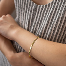 Load image into Gallery viewer, close-up woman's hand, with, Gold plated adjustable bracelet stamped with earth's longitude and latitude coordinates