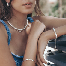 Load image into Gallery viewer, Female in a blue knitted top. She is wearing a silver chain and pearls necklace, and bracelet