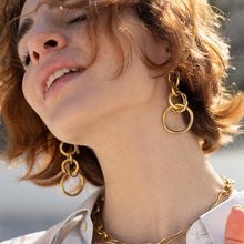 Load image into Gallery viewer, Brunette girl in profile. She is wearing a gold round link, loop earring