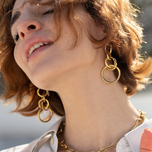 Brunette girl in profile. She is wearing a gold round link, loop earring