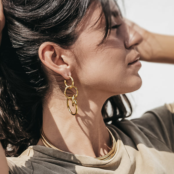 girl in profile. She is wearing a gold round link, loop earring