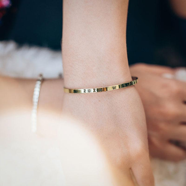 Close up of a female's left wrist. She is wearing a gold plated charm bracelet, stamped with the phrase 2020 Wishes