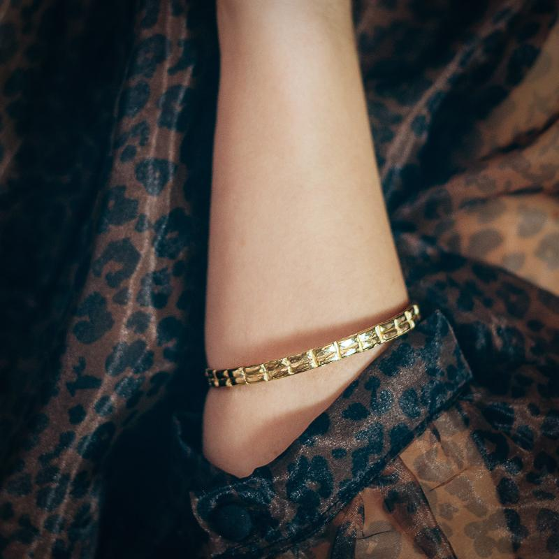 Close up of a left forearm. Semi transparent, patterned blouse, is rolled up. A gold bangle bracelet is worn