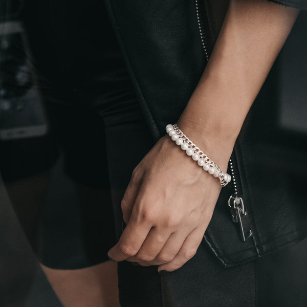 Close up of female hand wearing a silver chain and pearls bracelet by 3rd Floor