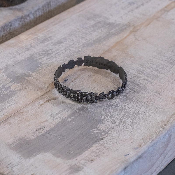 Hippolyta. Black bangle bracelet, with embossed intertwined flowers, placed on an etched wooden surface