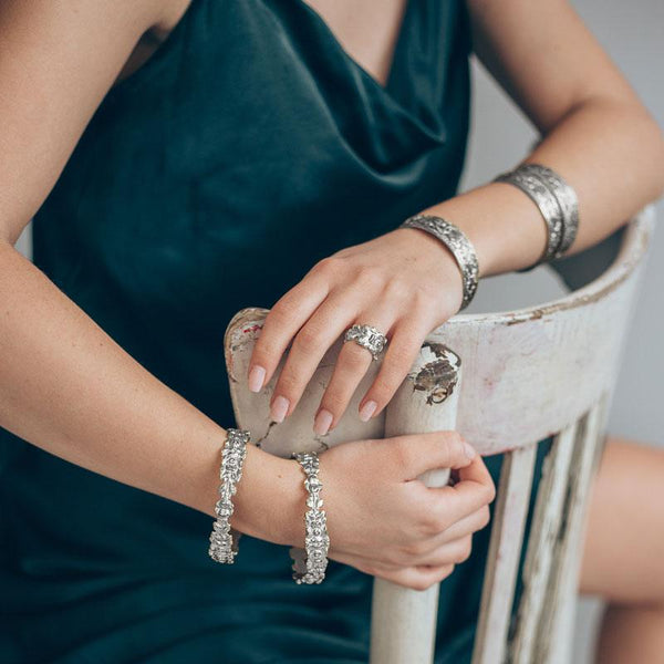 Close up photo, of a female, sitting on a white chair. Photo is cropped from chest to knees. She is wearing silver bracelets bracelets and ring