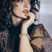 Load image into Gallery viewer, Brunette female. Her left hand up to her face. On her wrist, she is wearing a Kendra, gold, two toned, curve chain bracelet. By 3rd Floor