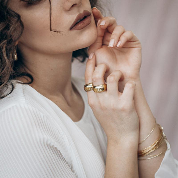 Cropped photo from nose to upper arm, of a brunette female in a white blouse. She is wearing gold rings on her right hand, and gold bracelets on her left
