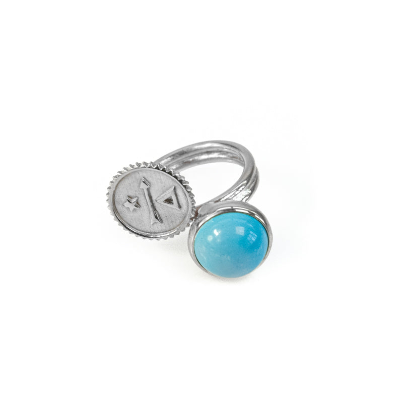 Silver, adjustable ring, with a turquoise stone, and a round, symbol embossed plate