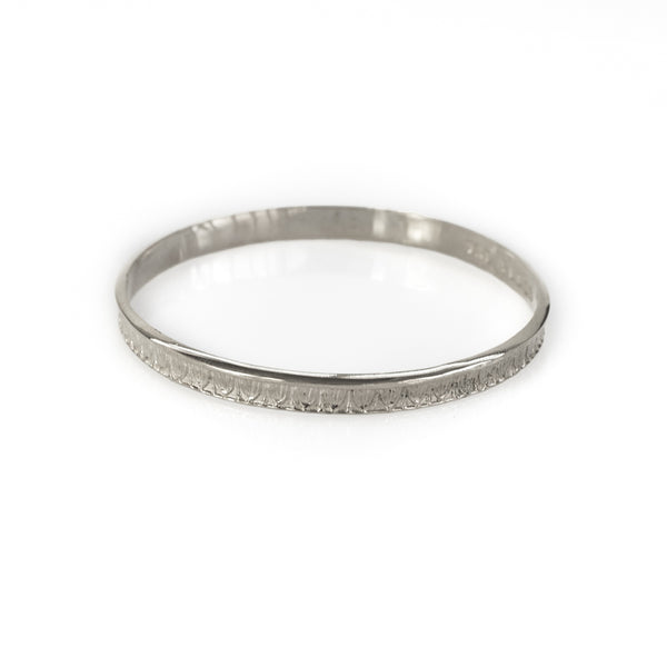 Photo of a silver, rod bracelet, with embossed designs. By 3rd Floor Handmade Jewellery