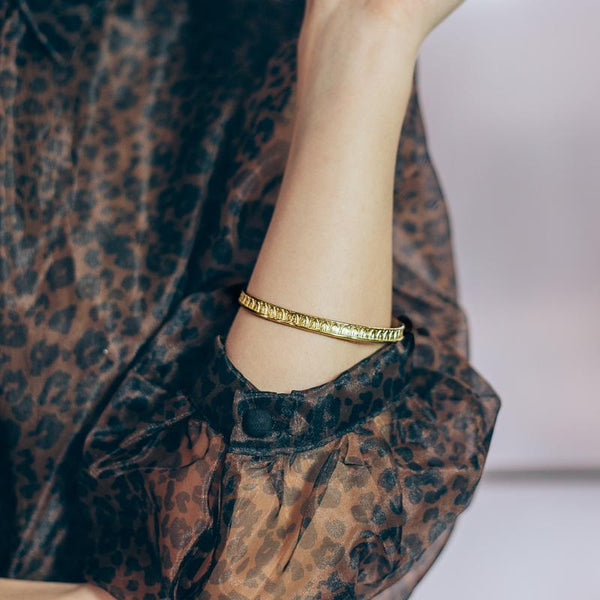 Female's forearm. She is wearing a semi-transparent pattern blouse, and a gold, flat rod bracelet