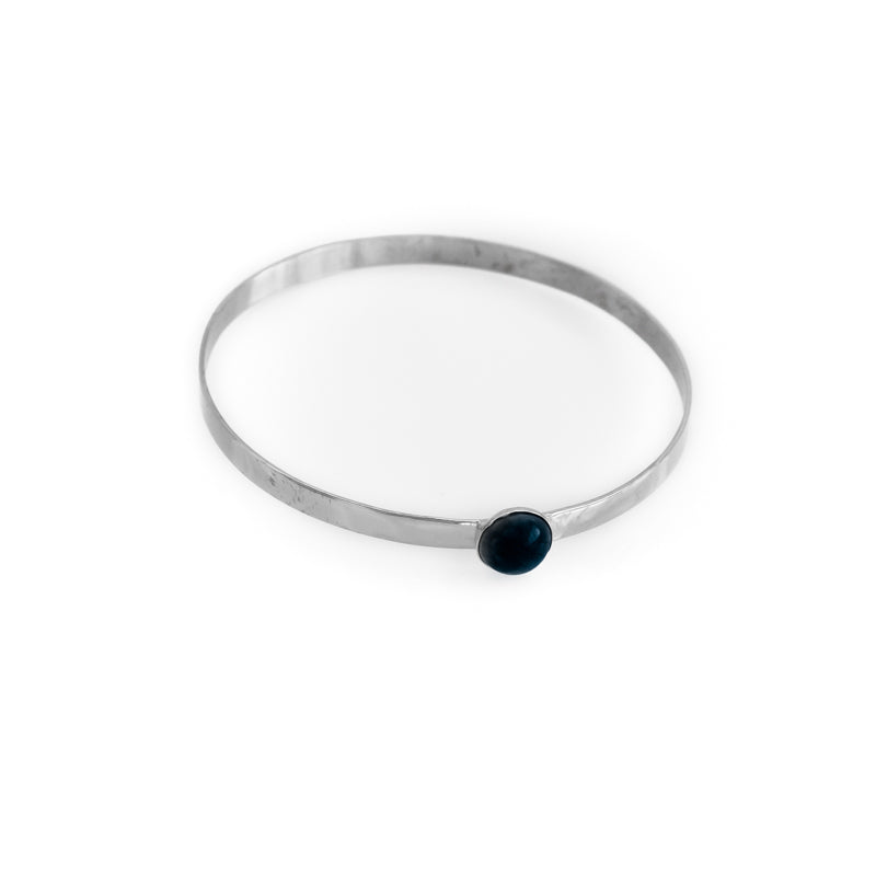 Odette. Silver, flat, bangle bracelet with a small, black onyx stone. By 3rd Floor Handmade Jewellery