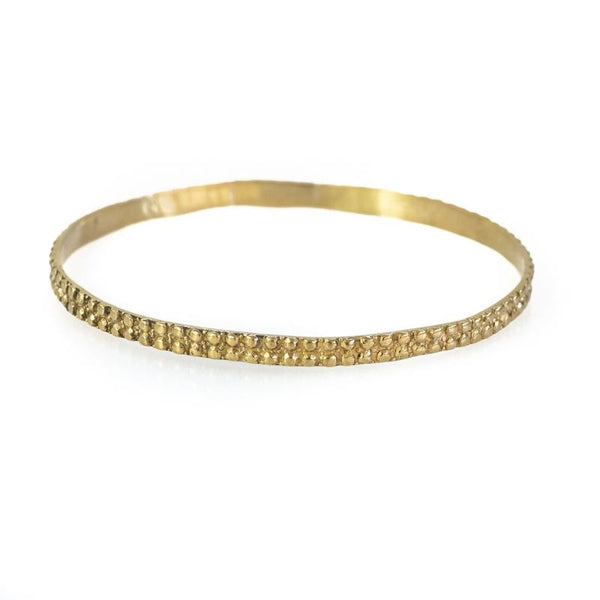 Photo of a gold bangle bracelet with embossed design. By 3rd Floor Handmade Jewellery
