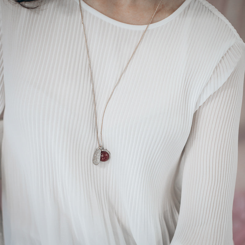 Cropped photo of an individual in a white blouse, wearing a silver, chain necklace with a brown carnelian semi precious stone