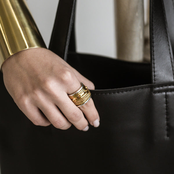 Photo of a female's hand, wearing a wide, gold ring on her right index finger. Traveller Greece ring by 3rd Floor
