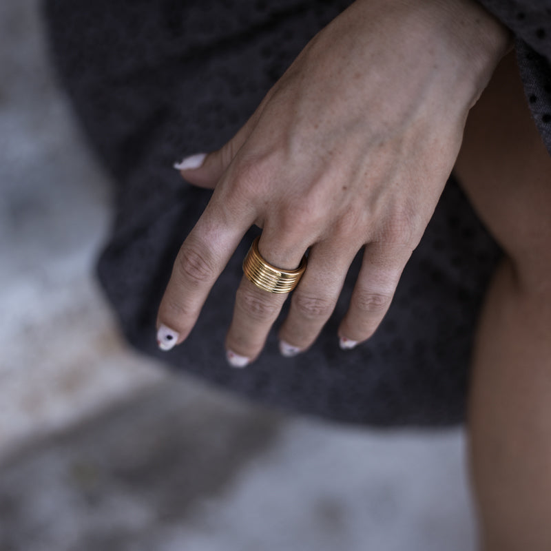 Close up of female's hand. On her middle finger, she is wearing, a Verona, handmade, gold plated ring, by 3rd Floor