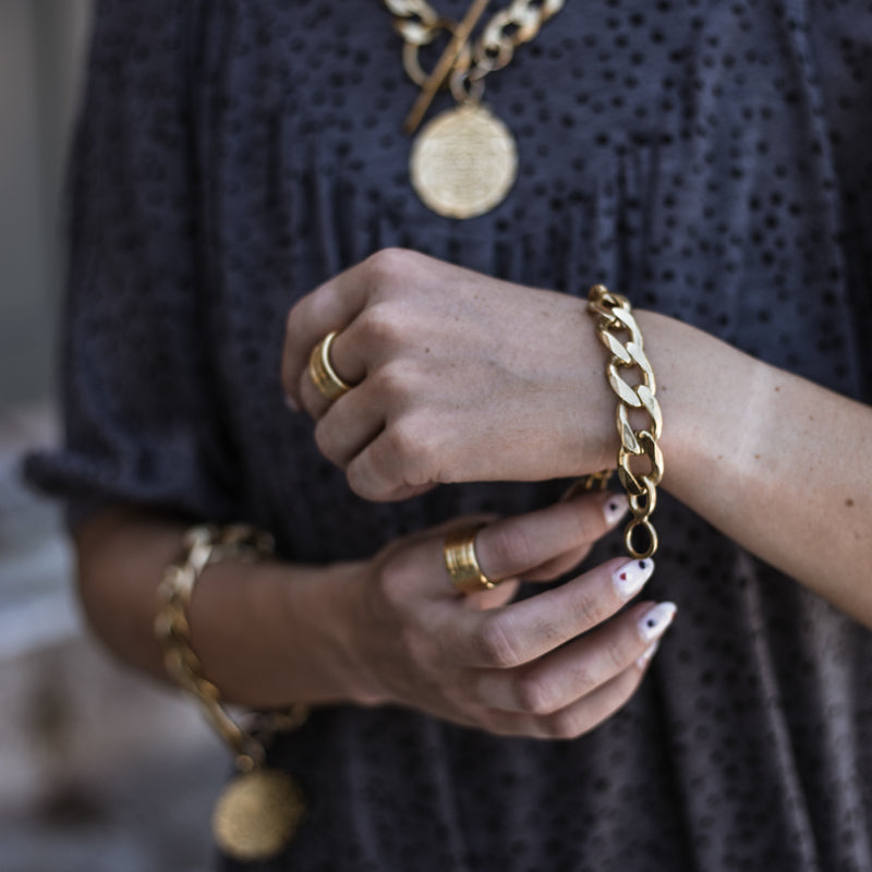 Close up of female's hands. On her left wrist she is wearing a Bilboe, handmade, silver plated brass, bracelet. On her right index finger she is wearing a Verona, gold ring