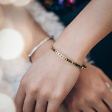 Load image into Gallery viewer, Female hands, right, crossed over the left. On her left wrist, she is wearing a gold plated, charm bracelet stamped with the phrase 2020 Wishes