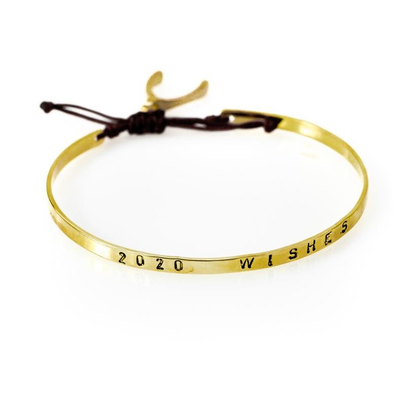 Handmade, gold plated, adjustable string bracelet stamped with the phrase 2020 Wishes. A wishbone hangs from the bracelet's black cord, tie