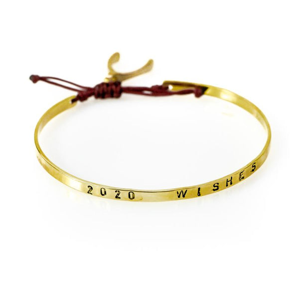 Handmade, gold plated, adjustable string bracelet stamped with the phrase 2020 Wishes. A wishbone hangs from the bracelet's red cord, tie