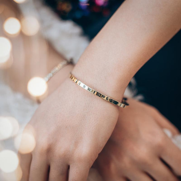 Female hands, right, crossed over the left. On her left wrist, she is wearing a gold plated, charm bracelet stamped with the phrase 2020 Wishes