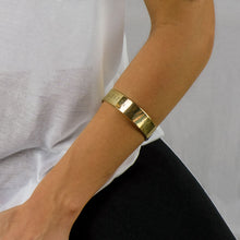 Load image into Gallery viewer, Forearm of a person wearing a gold bracelet stamped with earth's coordinates by 3rd Floor Handmade Jewellery