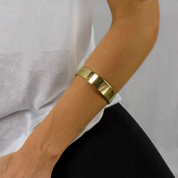 Forearm of a person wearing a gold bracelet stamped with earth's coordinates by 3rd Floor Handmade Jewellery
