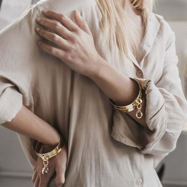 Blond female in a beige shirt. On her wrists, she is wearing, gold, double bangle, Vogue bracelets, by 3rd Floor