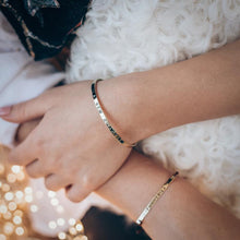 Load image into Gallery viewer, Close up of female's hands. Her left hand is touching her right forearm. On both wrists, she is wearing, silver, bracelets