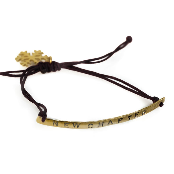 Gold, thin rod, cord wristlet, which ties with a black cord. A gold snowflake hangs from the cord. The wristlet is stamped with the phrase New Chapter