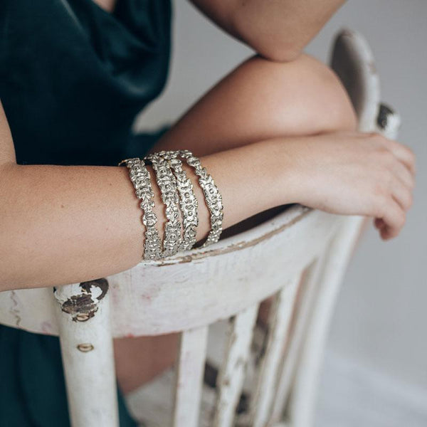 Close up photo of female's forearm. She is wearing 4 silver, bangle bracelets with embossed intertwined flowers