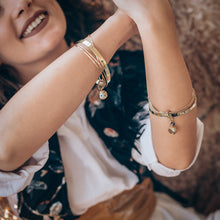 Load image into Gallery viewer, Happy, brunette girl, wearing handmade, gold, charm bracelets, on either wrist