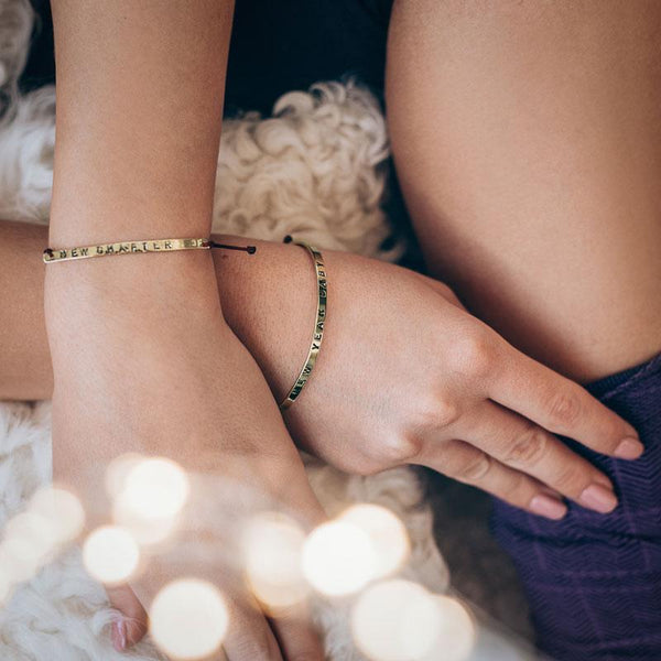 Close up of female hands, left crossed over the right. On her wrists, she is wearing thin, gold, charm bracelets by 3rd Floor Handmade Jewellery