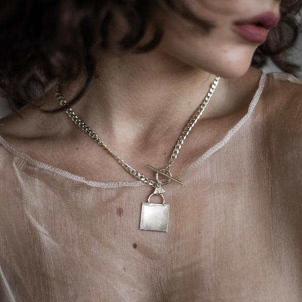 woman wearing Invicta. Handmade, flat curve chain, square pendant. Made in, 925 silver. By 3rd Floor Handmade Jewellery