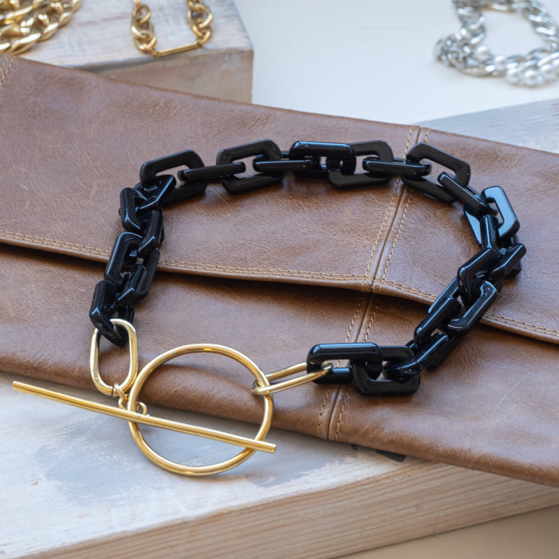 Black, square link necklace, with a gold, clasp buckle, placed on a brown wallet