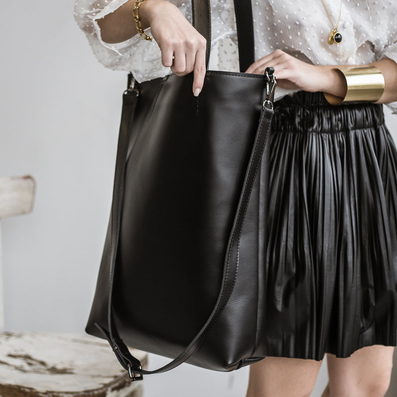 close up, woman wearing a black madeleine leather bag,by 3rd-floor workshop