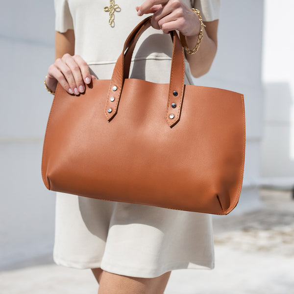 close up woman, is holding a handmade, leather Jet Set Mini handbag brown
