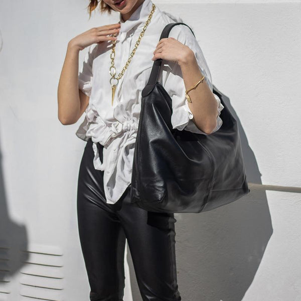 model holding Black shoulder bag, with wide shoulder strap. By 3rd Floor