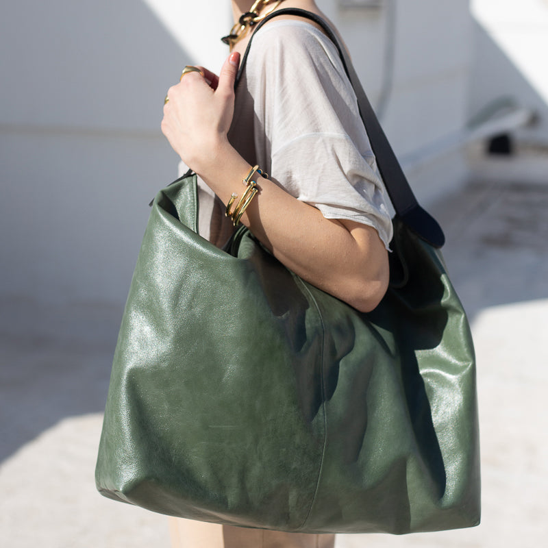model holding green shoulder bag, with wide shoulder strap. By 3rd Floor