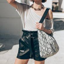 Load image into Gallery viewer, model holding Black and white shoulder bag, with wide shoulder strap. By 3rd Floor