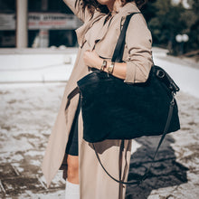 Load image into Gallery viewer, Cropped photo, from neck to knee, of a female in a tan trenchcoat. She is carrying a black, Vogue bag