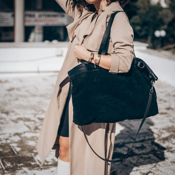 Cropped photo, from neck to knee, of a female in a tan trenchcoat. She is carrying a black, Vogue bag
