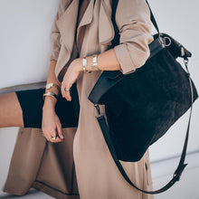 Load image into Gallery viewer, Female in tan trench coat, holding an over the shoulder, handmade, black suede bag