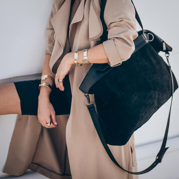 Female in tan trench coat, holding an over the shoulder, handmade, black suede bag