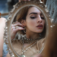 Load image into Gallery viewer, model looking to the mirror wearing Massive, loop chain earrings, in silver plated brass