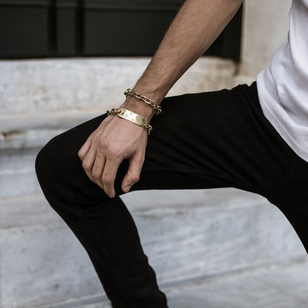 Male in black pants and white t-shirt. On his right hand, he is wearing two gold colored, bracelets. One link chain, and one ID bracelet