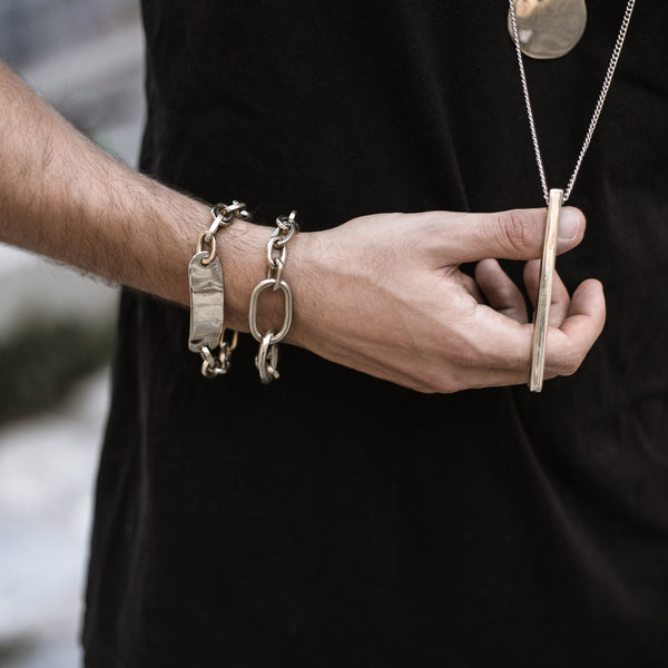 Cropped photo of male, wearing black. He is wearing two silver bracelets. With his right hand he is holding, a long, square, rod, chain necklace