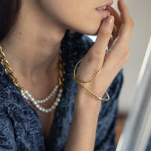 Load image into Gallery viewer,  brunette female, wearing a gold, statement bracelet by 3rd Floor Handmade Jewellery
