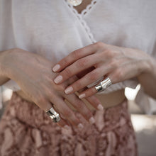 Load image into Gallery viewer, close-up woman's hands, with 3rd-floor handmade Punch rings, silver