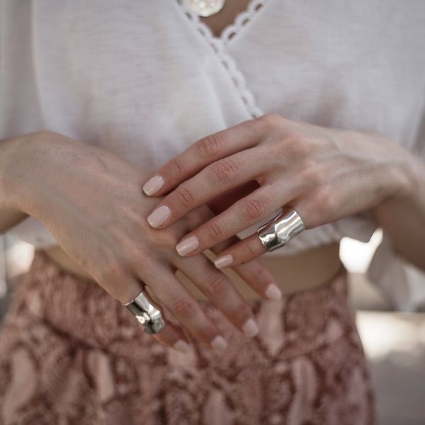 close-up woman's hands, with 3rd-floor handmade Punch rings, silver